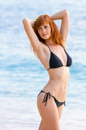 Young woman in bikini posing on sea coast standing photo