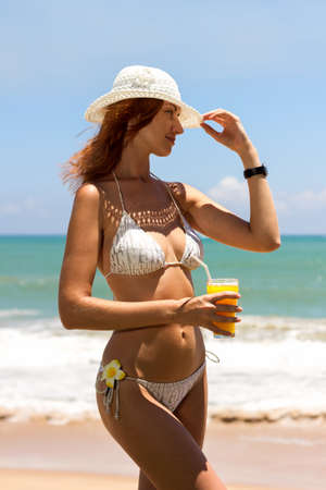swimsuite: Young woman in bikini with cocktail on the beach