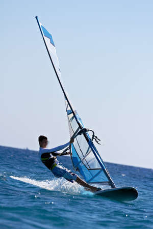Side view of a windsurfer passing by Standard-Bild