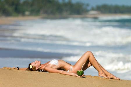 Jonge vrouw in bikini met cocktail op het strand liggen