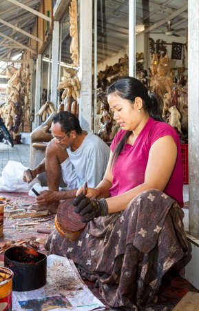 saturating: A woman is saturating with stain wooden crafts  in Indonesia Editorial