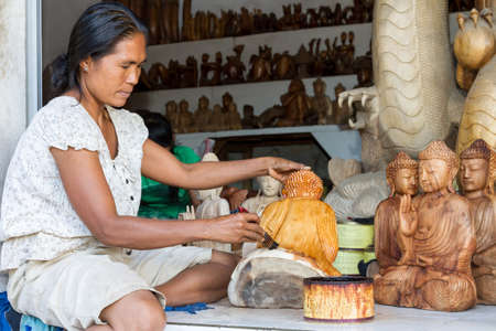 saturating: A woman is saturating with stain wooden Buddha  in Indonesia Editorial
