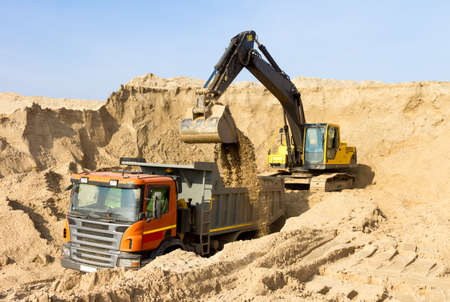 earth handful: Excavator Loading Dumper Truck Construction Site