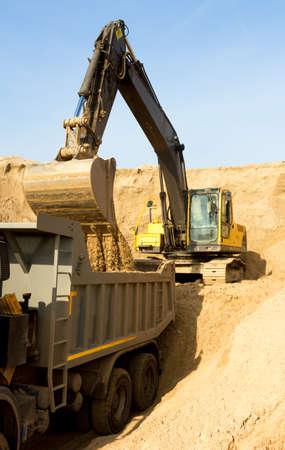 Excavator Loading Dumper Truck at Construction Site
