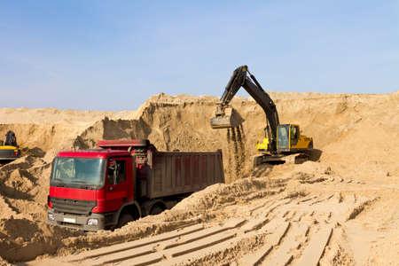 dumper truck: Excavator Loading Dumper Truck at Construction Site