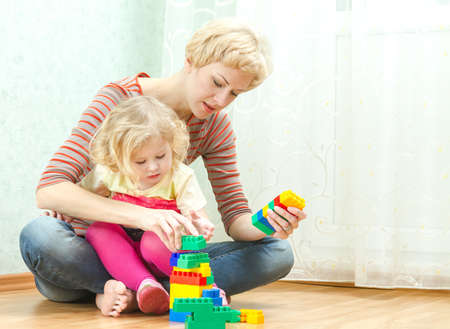 Mother with a little daughter playing with blocks photo