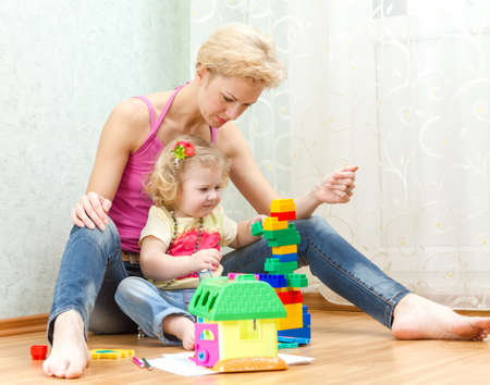 motherly: Mother with a little daughter playing with blocks