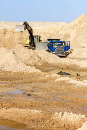 front end: Excavator Loading Dumper Truck at Construction Site