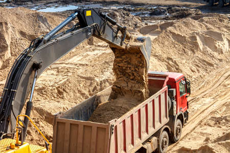 Excavator Loading Dumper Truck at Construction Site