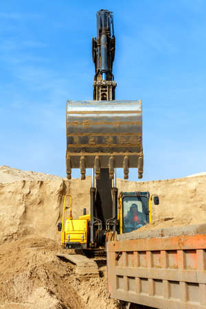 earth handful: Excavator Loading Dumper Truck at Construction Site