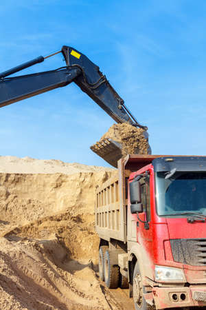 Excavator Loading Dumper Truck at Construction Site photo