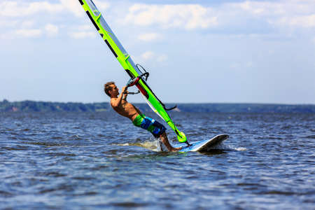Side  view of young windsurfer starting a falli photo
