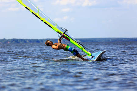 Side view of a windsurfer falls to water photo
