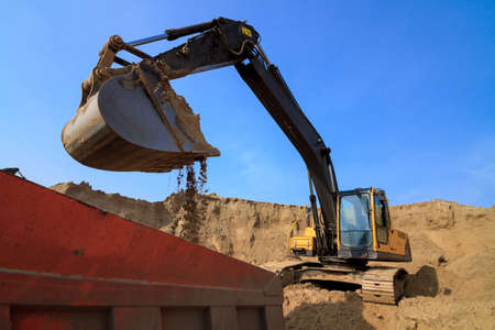 Excavator Loading Dumper Truck at Construction Site Stock Photo - 21818376