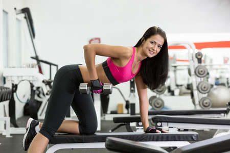 Young women do a workout at the gym looking in camera photo