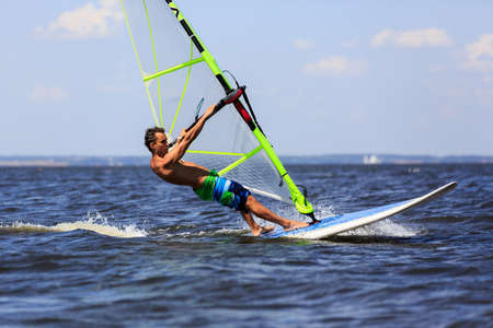 Young man windsurfing with trailing wake