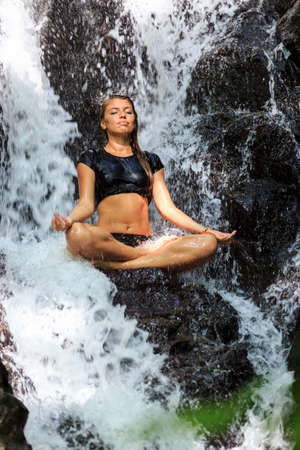 Young woman enjoying in yoga pose in Waterfall photo