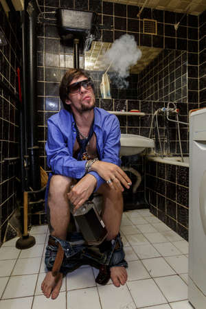 man smoking: Drunk Man sits in a toilet with a bottle of whiskey and smoking,