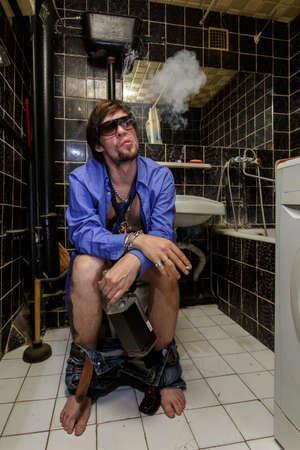 hombre fumando: Hombre borracho sentado en un inodoro con una botella de whisky y fumar,