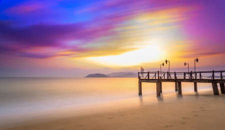 Long exposure of magic unreal colorful sunrise and wooden pier, Nha Trang City Beach, Vietnam Stock Photo