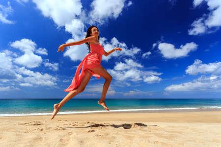 jeune fille: Bonne fille en robe rouge sauter et courir sur la plage