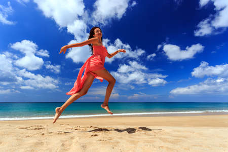 woman beach dress: Happy girl in red dress jumping and running on beach