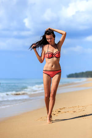 attractive girl: young girl in red bikini walking at tropical beach