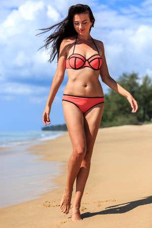 femme brune sexy: jeune fille en rouge bikini marche � la plage tropicale