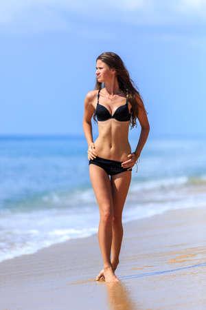 traje de bano: Chica en bikini negro caminando en la playa tropical Foto de archivo