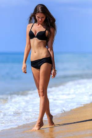 black girl: Junges M�dchen im schwarzen Bikini zu Fu� am tropischen Strand
