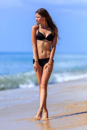 jolie fille: Jeune fille en noir bikini marche � la plage tropicale