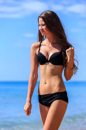 sexy young girl: Young girl in black bikini posing at tropical beach