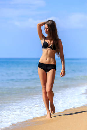 woman body: Young girl in black bikini walking at tropical beach