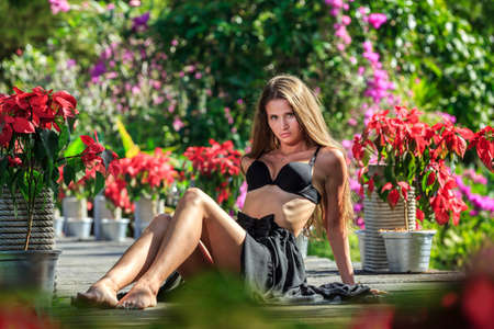 young adult woman: Young woman in black dress sitting in the tropical park