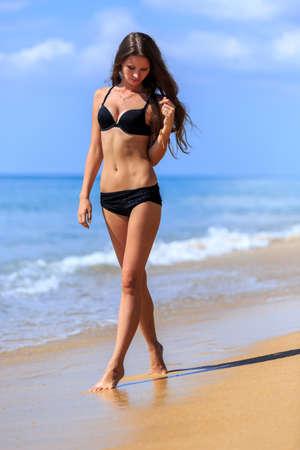 cuerpo femenino: Chica en bikini negro caminando en la playa tropical Foto de archivo