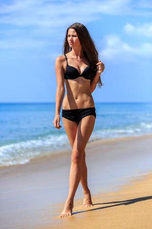 sexy young girl: Young girl in black bikini walking at tropical beach