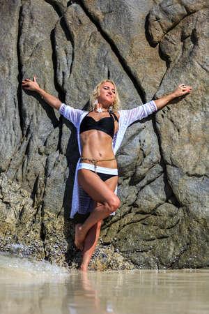 traje de bano: Mujer joven que presenta detr�s de la roca en la playa tropical Foto de archivo