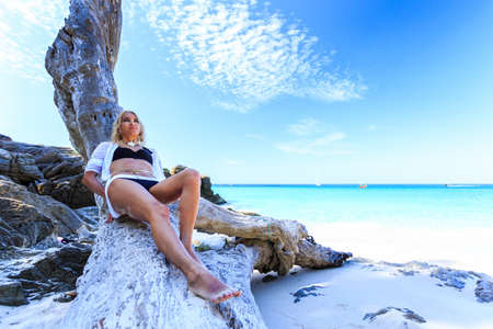 hot day: Young woman relaxing on the tree at tropical beach Stock Photo