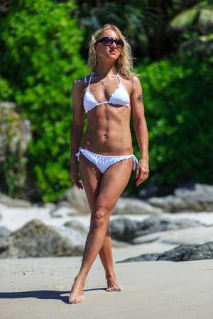 traje de bano: mujer joven que recorre en una playa tropical en Tailandia Foto de archivo