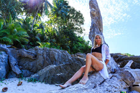 attractive girl: Young woman relaxing on the tree at tropical beach Stock Photo