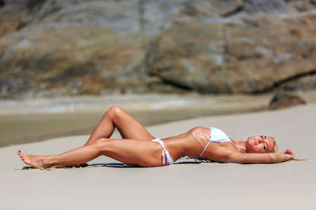 girl pose: Young woman is lying on a tropical beach Stock Photo