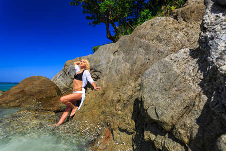 hot stone: Young woman posing behind the rock at tropical beach