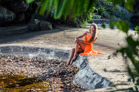 Young woman in orange dress sitting in the tropical park