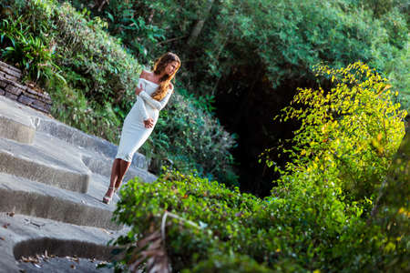 shifted: Young woman in white dress posing on stairs in the tropical park. Shifted horizon Stock Photo