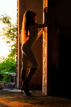 building silhouette: Silhouette of beautiful girl posing in an abandoned building Stock Photo