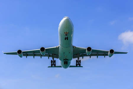 aerospace industry: airplane landing in bright Blue sky, right before touch-down