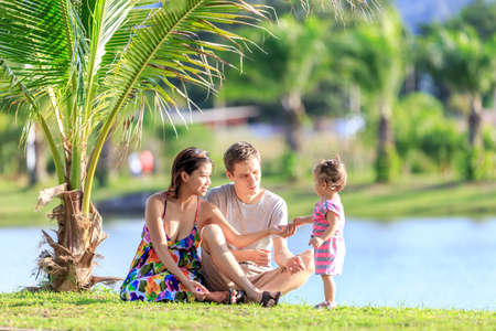 tropical garden: happy young family spending time in a tropical garden on a summer day