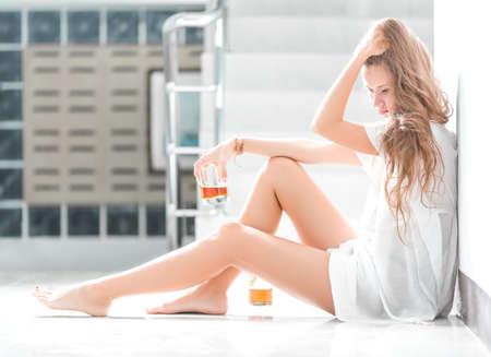 Girl in depression sitting on the floor with glass of wine