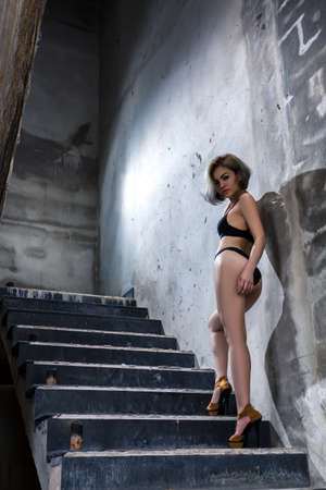 Beautiful girl posing on stairs in the abandoned building