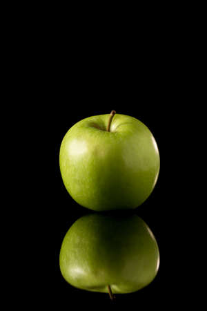 Fresh green apple on a black reflective background, Studio shot,